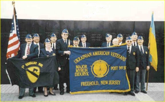 Ukrainian American Veterans (UAV) Post 30 members holding post flag at tribute to their patron, Major Myron Diduryk, at the inscription of his name on the New Jersey Vietnam Veterans Memorial in Holmdel, NJ